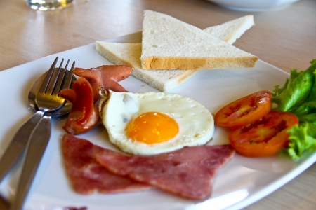 american breakfast with egg,ham,bread and sausage