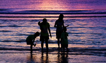 family play on the beach in sunrise background at Hua Hin beach, Thailand  photo