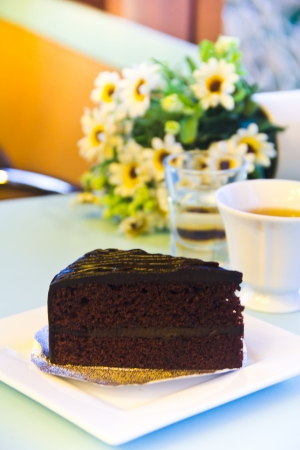 chocolate cake with banana and a cup of tea on table