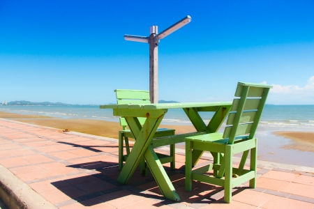 longue: green wooden chairs and table on beach