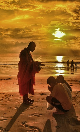 男はホアヒンのビーチで僧侶のために祈る。タイ。