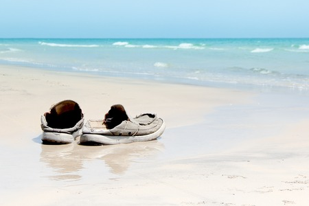 美しいビーチでの古い靴
