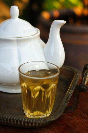 a cup of tea and tea pot on table Stock Photo