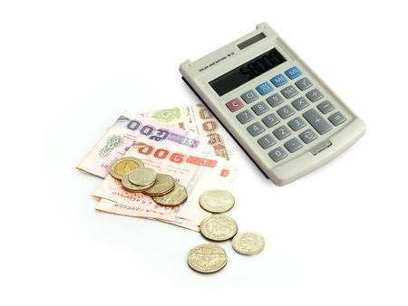 電卓、タイの紙幣および白い背景の上のコイン