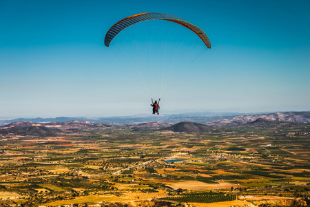 parapente: A paraglider flies over picturesque fields in the background of blue sky
