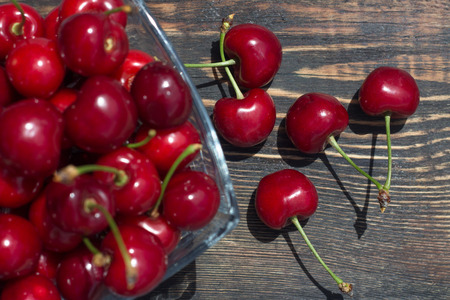 ripe cherry berries in a glass vase on a dark wooden background