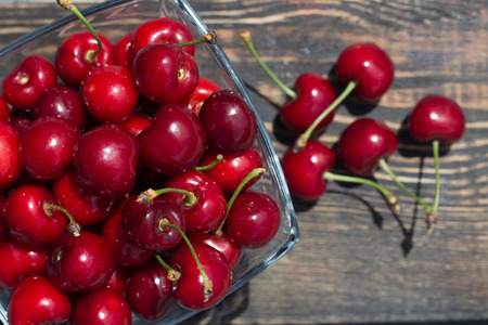 red cherries in a glass vase on a dark background