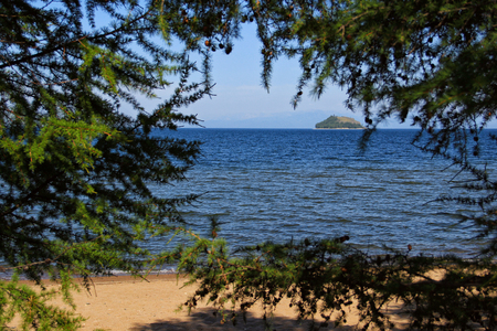 Landscape with the image a small island in the bay of lake Baikal through the trees