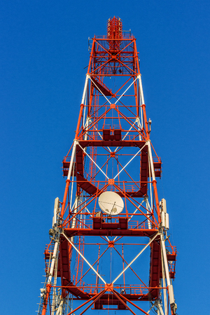 Telecommunication tower with antennas on a background of blue sky. Television and radio tower in a big city.