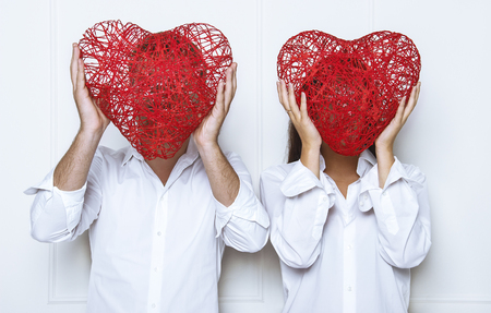 Man and a woman, standing in front of a white wall and hiding the face behind the red, braided heart. Romantic photoshoot on Valentines Day. Stock Photo