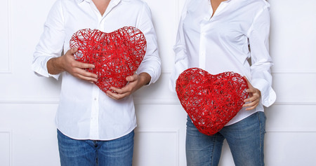 Man and a woman dressed in a white shirt and blue jeans holding red wicker hearts. Romantic photo session in the studio on Valentines Day.