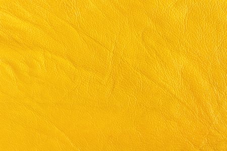 Surface leather substitute with creases and wrinkles in yellow color, tissue sampling.  background, texture. Stock Photo