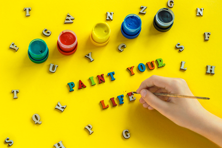Lettering Paint your life from colorful letters, hand with paintbrush, gouache, scattered wooden letters. yellow background, greeting card. Concept - Paint your life. It's up to you Фото со стока