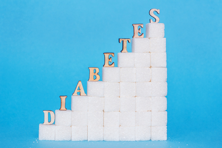 Word diabetes on ladder refined sugar, blue background. Ð¡oncept much sugar leads to increased blood sugar levels and diabetes mellitus Stock Photo