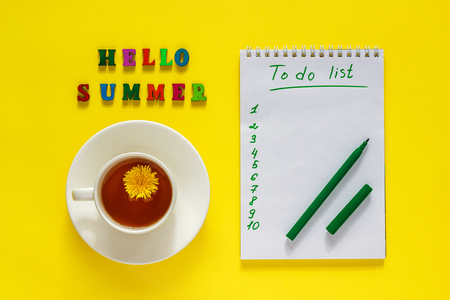 Lettering Hello summer, сup of tea with dandelion,  To Do List, pen. Still life on yellow background. Concept  to-do list for summer holidays or vacation