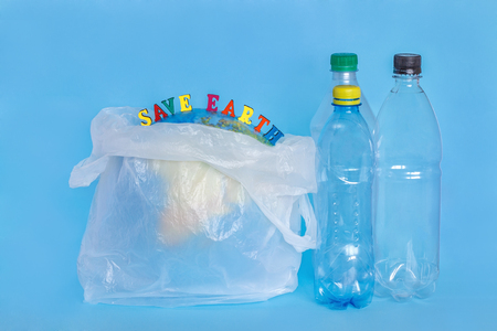inscription SAVE EARTH, plastic bottles, abstract earth in polyethylene bag, blue background. Concept ecology problem of environmental pollution planet by plastic Earth Day, World Environment Day