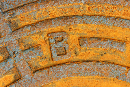 Fragment of a rusty iron city sewer hatch. background, texture. Closeup.