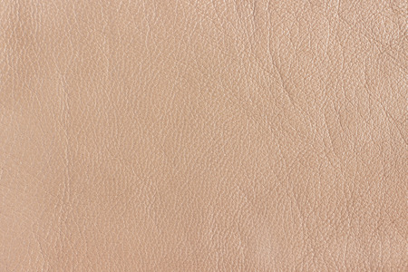 Surface of the animal skin with folds and wrinkles beige. Leather as a background or seamless texture.