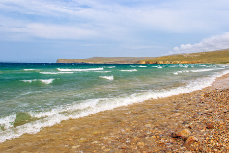 Landscape with the image of clear, windy weather and small waves rushing to the pebbled shore of Lake Baikal. Stock Photo