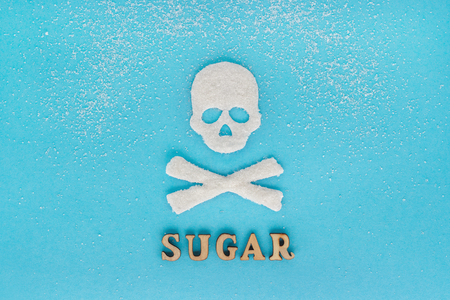 Skull bones sugar, scattering of granulated sugar, Text SUGAR,  blue background. concept - greater consumption of sugar kills. Concept - large amount of sugar kills