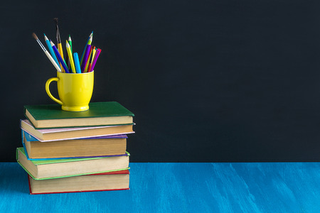 Concept Education Workplace pupil Books Stationery on blue table on background black chalkboard Layout Copy space