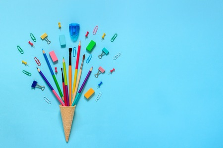 Stationery Pencils paintbrush paperclip in waffle ice cream cone. Still life on blue background. Copy space Flat lay Top view Concept Education Stock Photo
