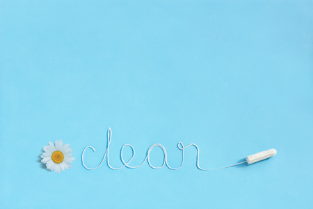 Word CLEAN from white thread hygienic female tampon and chamomile on blue background. Concept hygiene and health women and adolescents during menstrual cycle. Flat Lay, copy space