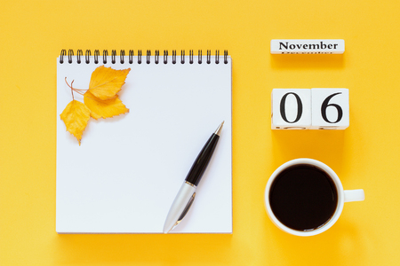 Autumn composition. Wooden calendar November 6 cup of coffee, empty open notepad with pen and yellow oak leaf on yellow background. Top view Flat lay Mockup Concept Hello November 免版税图像