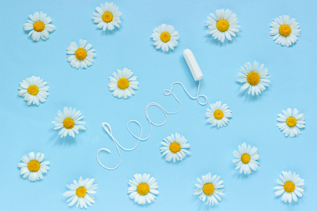 Word CLEAN from white thread hygienic female tampon surrounded by chamomile flowers on blue background. Concept hygiene and health women and adolescents during menstrual cycle. Flat Lay