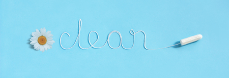 Word CLEAN from white thread hygienic female tampon and chamomile on blue background. Concept hygiene and health women and adolescents during menstrual cycle. Flat Lay