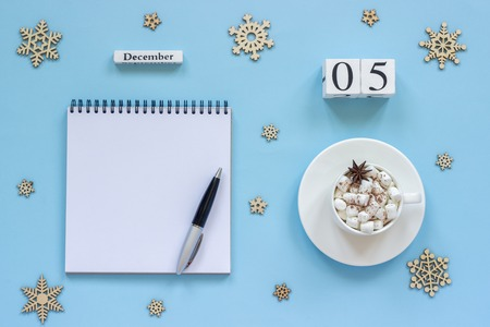 Winter composition. Wooden calendar December 5 Cup of cocoa with marshmallow and star anise, empty open notepad with pen and snowflake on blue background. Top view Flat lay Mockup Concept