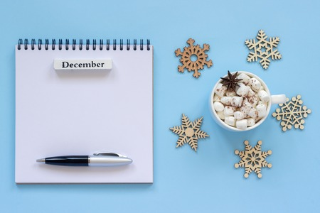 Winter composition. Wooden calendar month December Cup of cocoa with marshmallow and star anise, empty open notepad with pen and snowflake on blue background. Top view Flat lay Mockup Concept