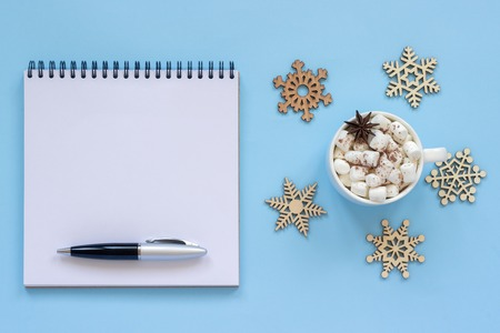 Winter composition. Cup of cocoa with marshmallow and star anise, empty open notepad with pen and snowflake on blue background. Top view Flat lay Mockup Concept