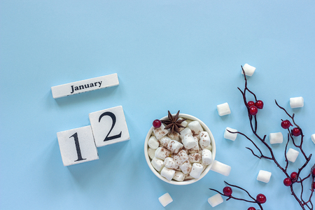 Winter composition. White wooden calendar cubes. Data January 12. Cup of cocoa, marshmallows and decorative branch with red berries on blue background Top view Flat lay Copy space Фото со стока