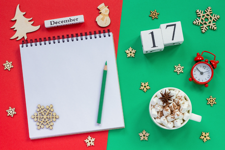 Winter composition. Wooden calendar December 17th Cup of cocoa with marshmallow, empty open notepad with pencil, snowflake, alarm clock on red and green background. Top view Flat lay Mockup 版權商用圖片