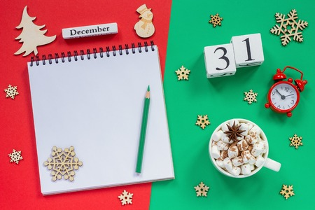 Winter composition. Wooden calendar December 31st Cup of cocoa with marshmallow, empty open notepad with pencil, snowflake, alarm clock on red and green background. Top view Flat lay Mockup Stock Photo