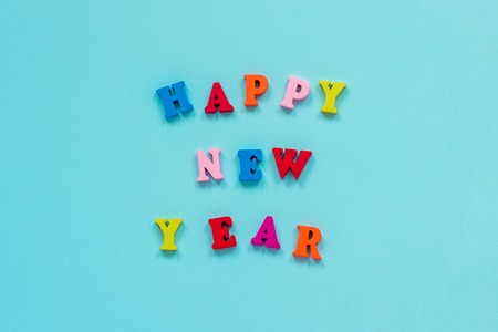 Text Happy New Year of bright multicolored wooden letters on blue background. Top view Greeting card