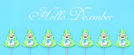 Text Hello December, Candy lollipop of funny snowman and Christmas tree on blue background. Flat lay, Top view, Banner greeting card Stock Photo