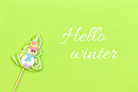 Text Hello winter and candy lollipop of funny snowman, Christmas tree on green background. Top view, Greeting card Stock Photo