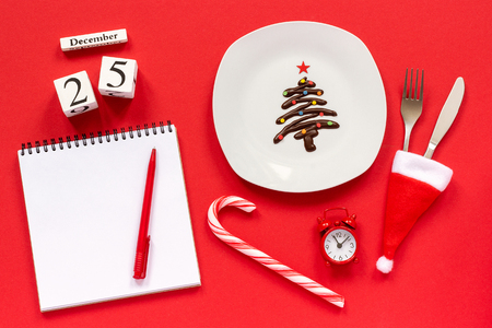 Christmas composition Calendar December 25th. Sweet chocolate Christmas tree on plate and cutlery in santa hat. Empty notepad with pen, cane, alarm clock on red background. Flat lay Top view Stock Photo