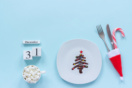Calendar December 31st. Sweet chocolate Christmas tree on plate, cutlery in santa hat and cup of cocoa with marshmallow on blue background. Flat lay Top view Concept New Years treat at festive table Stock Photo