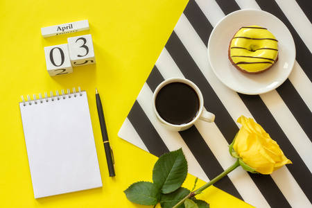 Wooden cubes calendar April 3rd. Cup of coffee, yellow donut and rose on black and white napkin, empty open notepad for text on yellow background. Concept stylish workplace Top view Flat lay Mockup Banco de Imagens