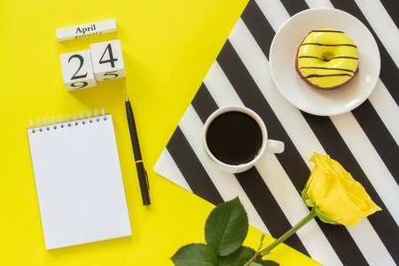 Wooden cubes calendar April 24th. Cup of coffee, yellow donut and rose on black and white napkin, empty open notepad for text on yellow background. Concept stylish workplace Top view Flat lay Mockup