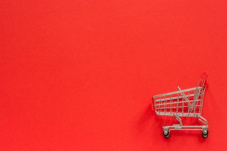 Small empty shopping trolley cart on red background. Concept sale. Top view Copy space.