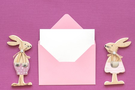 Romantic composition Pair of wooden lovers figurine rabbits and pink envelope with blank card on purple background Concept Valentines card Top view Flat Lay Mockup. Imagens