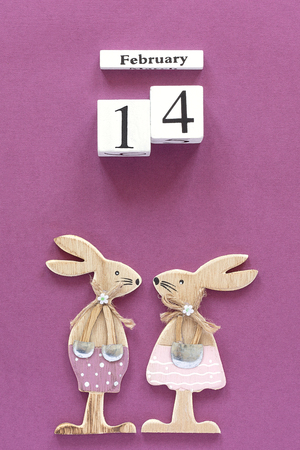 Romantic composition Wooden cubes calendar February 14th and pair of wooden lovers figurine rabbits on purple background. Concept Valentines card. Top view Flat Lay.