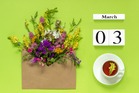 Wooden cubes calendar March 3. Cup of herbs tea, kraft envelope with multi colored wildflowers on green background. Concept hello spring Creative Top view Flat lay.