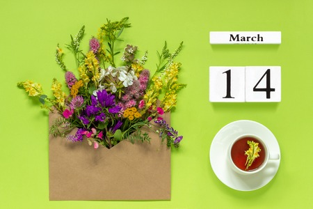Wooden cubes calendar March 14. Cup of herbs tea, kraft envelope with multi colored flowers on green background. Concept hello spring Creative Top view Flat lay. Фото со стока