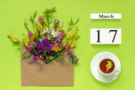 Wooden cubes calendar March 17. Cup of herbs tea, kraft envelope with multi colored flowers on green background. Concept hello spring Creative Top view Flat lay.