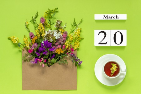 Wooden cubes calendar March 20. Cup of herbs tea, kraft envelope with multi colored flowers on green background. Concept spring equinox day Creative Top view Flat lay.